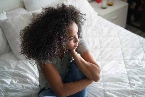 woman sitting in bed feeling depressed