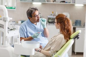 patient with red hair sitting in dental chair listening to dentist speak